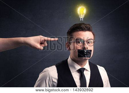 Caucasian hand pointing at businessman with a lightbulb above his head