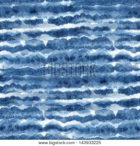 Seamless tie-dye pattern with horizontal stripes of indigo color on white silk. Hand painting fabrics - nodular batik. Shibori dyeing.