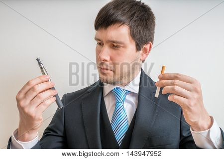Man (smoker) Is Comparing Classic Tobacco Cigarette And Electron