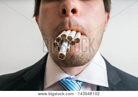 Young Man Has Full Mouth Of Cigarettes. He Wants To Smoke Many C