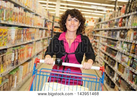 Curious Woman In The Supermarket Thinking What To Buy