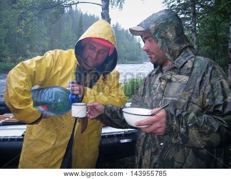 KOLSKYY RUSSIA - 13 AUGUST 2008: A man in a raincoat pours water from a bottle into a cup in rainy weather