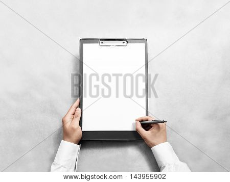 Hand signing blank black clipboard with white a4 paper design mockup. Clear document holder mock up template hold arm. Clip board notepad surface display front. Checklist tablet plan file presentation