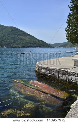 An old abandoned wooden boat upturned and forgotten about in the harbour of the historic Montenegrin town of Perast