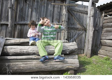 In the summer in the village on the street nabrevnah sitting little girl and boy and show ok.