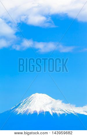 Fuji mountain in light blue color with white top of snow and wide sky above (copy space)