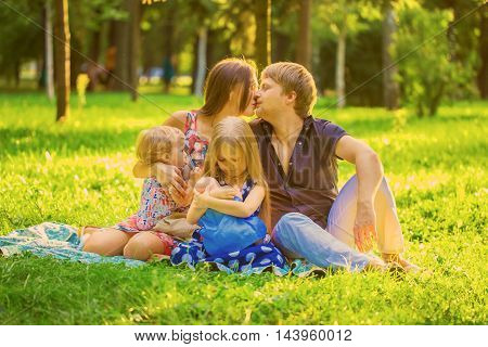 Happy family together at the picnic. Mother breastfeeding baby son little daughter is breastfeeding a doll.