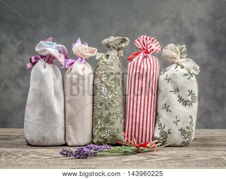 Group of decorative pouches staffed with dried lavender on wooden table
