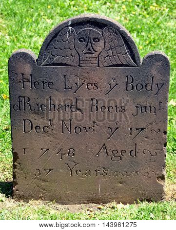 New York City - May 11 2012: Colonial-era 1748 gravestone with winged skull in the churchyard at historic Grace Episcopal Church in Jamaica Queens
