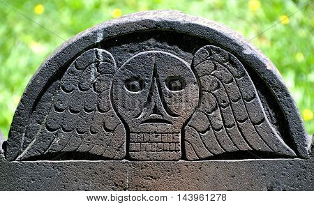 New York City - May 11 2012: Colonial 1748 gravestone with winged skull in the churchyard at historic Grace Episcopal Church in Jamaica Queens