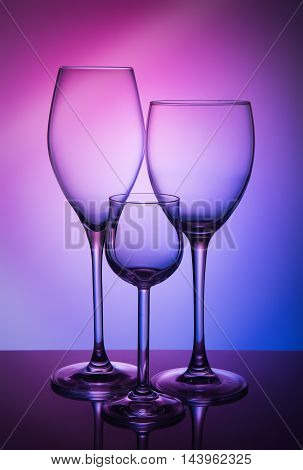 Three different wine glass on a color background