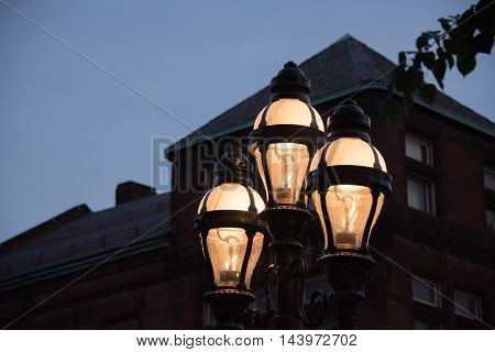Illuminated street light with three unusual shaped globular globes against the silhouette of a building in the darkness