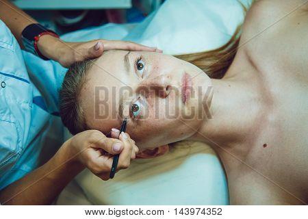 The workflow in a beauty salon girl plucked eyebrows. Tweezers.
