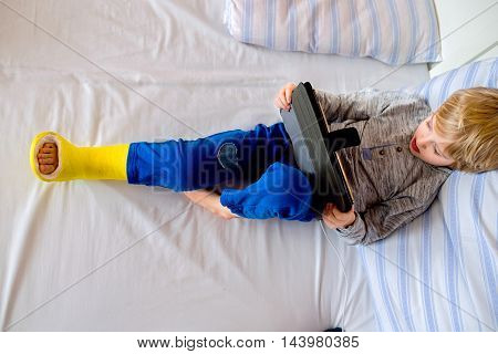 Little Boy With Broken Leg Playing On Tablet