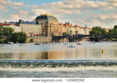 Prague Czech Republic-August 23 2016: View of the National Theatre with the people on the boats and pedal boats on the river Vltava