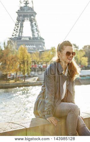 Smiling Elegant Woman Sitting On The Parapet In Paris, France
