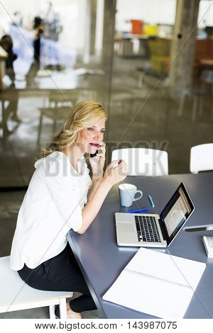Manageress With Mobile Phone In Office