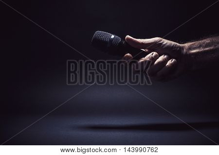 Conceptual composition male hand holding a microphone ready for an interview symbolically representing a freedom of speech.