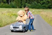Little preschool kid boy driving big toy car and having fun with playing with his plush toy bear, outdoors. Child enjoying warm summer day in nature landscape poster