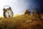 sand running out of a nostalgic alarm clock other watches sink into the sand surreal metaphor in a fantasy landscape concept of time passes by eventide or infinity selected focus very shallow depth of field poster