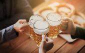 people, leisure and drinks concept - close up of hands clinking beer mugs at bar or pub poster