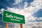 Safe Haven Green Road Sign with Dramatic Clouds, Sun Rays and Sky. poster