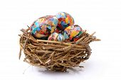 Bunch of paper collage eggs in bird's nest over white background poster