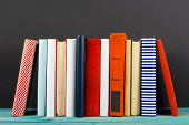 Composition with old vintage colorful hardback books, diary on wooden deck table and black board background. Books stacking. Back to school. Copy Space. Education background poster