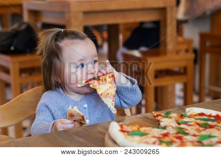Children Eat Italian Pizza In The Cafe. Adorable Little Girl Eating Pizza At A Restaurant