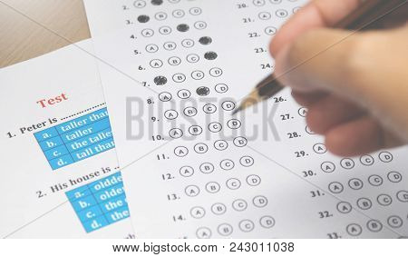 Multiple Choice Answer Sheet And English Test On Desk With Blur Hand Holding Pencil In Classroom