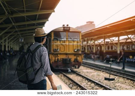 Young Asian Man Traveler With Backpack And Hat Standing And Holding Map Waiting Train For Travel At