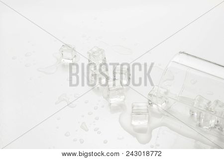 Spilled Glass Of Water With Ice On A Light Background.