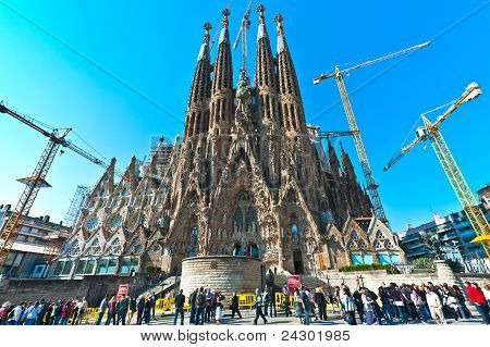 BARCELONA SPAIN 17 April: Tourists looking Sagrada Familia in 17.04.2011 in Barcelona Spain. Expiatory Church of Holy Family (Sagrada Familia) by architect Gaudi building is begun in 1882 poster