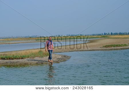 A Man In Blue Jeans And A Red Shirt Walking Along The River