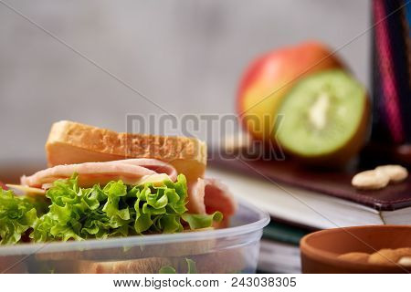School Or Picnic Lunch Box With Sandwich And Various Colorful Vegetables And Fruits On Wooden Backgr