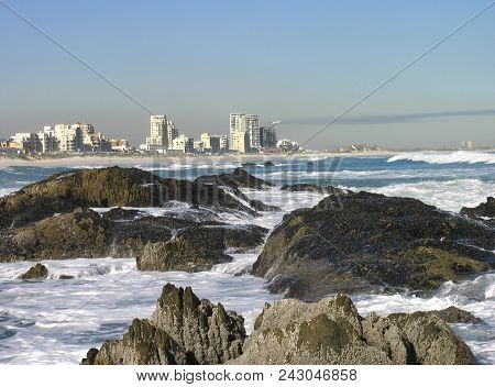 Seascape, With White Waves Washing Over Some Boulders In The Fore Ground, And High Rise Buildings In