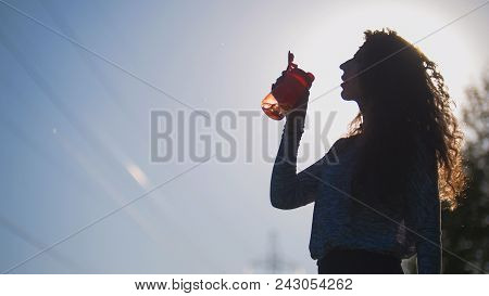 Cyclist Pulls Out Of The Backpack Water And Drinking Background Of The Sun, Sports In The Park, Legs