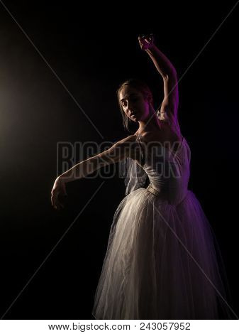 Ballerina Is Practicing Her Moves In Dark Studio. Young Girl Dancing With Air White Dress Tutu, Spin