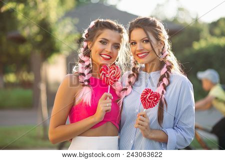 Pretty Girlfriends With Colorful Braids Holding Candy Heart On Stick Like Heart And Happy Smiling At