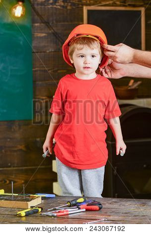 Toddler In Protective Hard Hat, Helmet At Home In Workshop. Child Cute And Adorable Stands While Mal