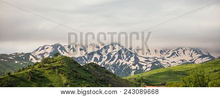 Mountains full of green trees and grass, but for background, heavy clouds cover the tops of snowy mountains make them look like military uniforms. Panoramic view, banner.