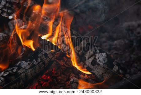 Fireplace with burning firewood and colorful blazes of fire on black background. Close up with details, space.