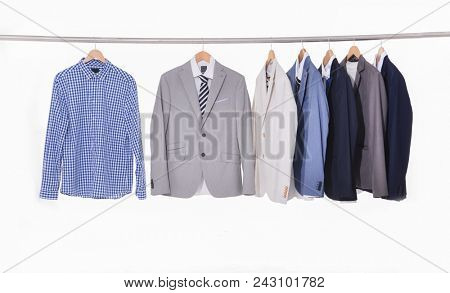 Set of Colorful Suits with shirts on hangers on white background