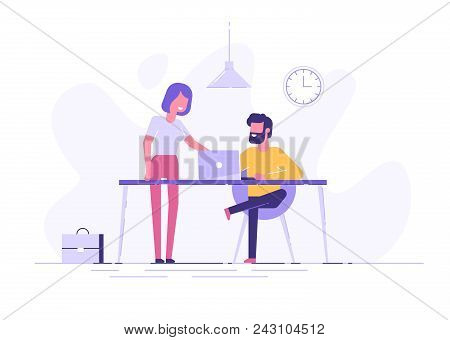 Young Man Is Sitting At A Desk With Computer And His Colleague Is Pointing To A Screen And Giving Ad