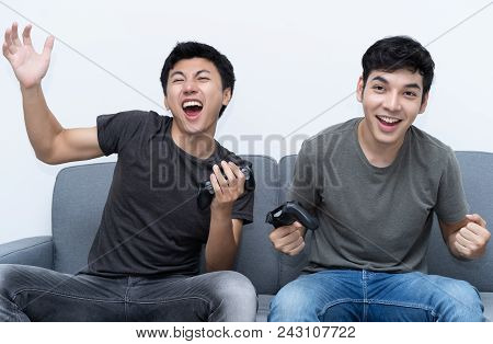 Two Young Gamer Playing Video Games Online And Celebrating The Team Success.