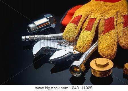 Plumbing Accessories On Textured Dark Background.