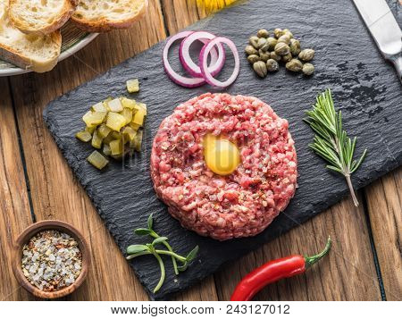 Steak tartare served with raw quail egg yolk and other tartare ingredient. Meat dish.