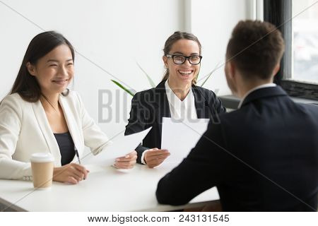 Positive Multiracial Hr Team Or Friendly Female Executives Laughing At Funny Joke During Successful