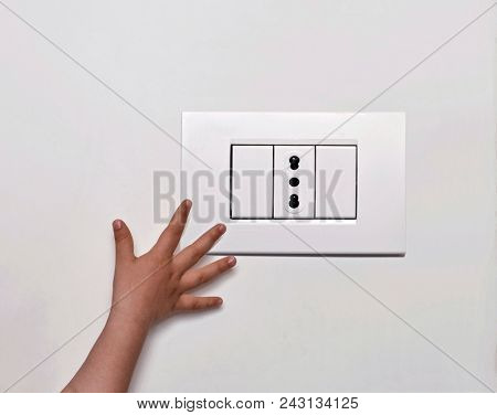 Kid hand approach power outlet. The danger of electricity for a kids