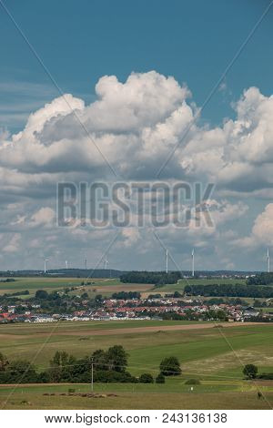 Little Village In The Middle Of The German Countryside With Forests, Fields And Meadows